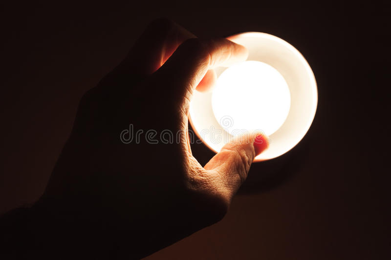 Male hand turning on small lamp stock photography
