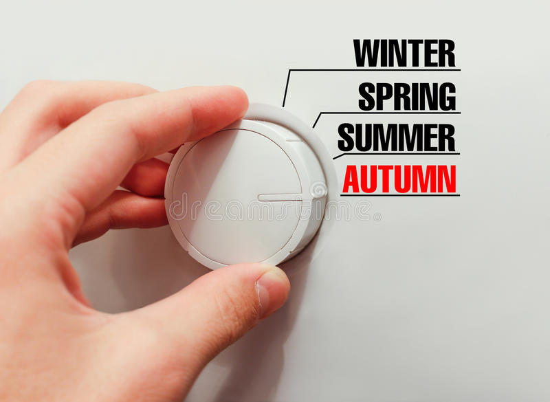 Male hand turns the switch. Switches seasons. Chose the autumn. Male hand turns the switch. Switches seasons. Chose the autumn stock photography