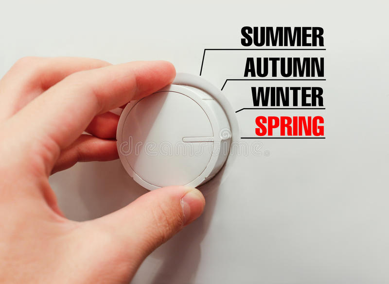 Male hand turns the switch. Switches seasons. Chose the spring. Male hand turns the switch. Switches seasons. Chose the spring stock image