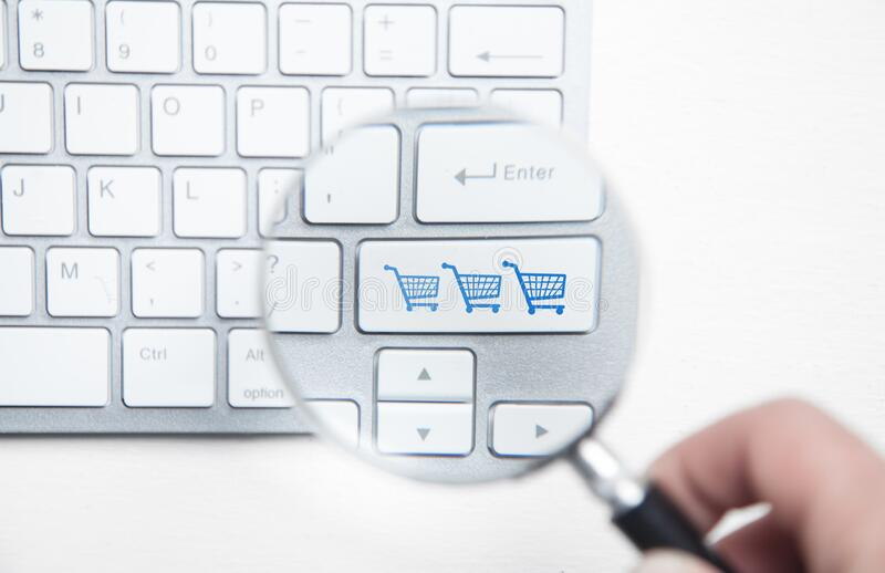 Male hand using magnifying glass. Shopping carts on computer keyboard. Online shopping royalty free stock images