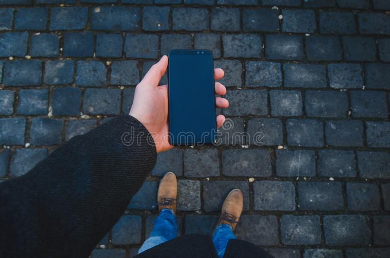 Male hand using smart phone on the street. Concept of technology and social network. Business man with watches, coat and take a ph stock image