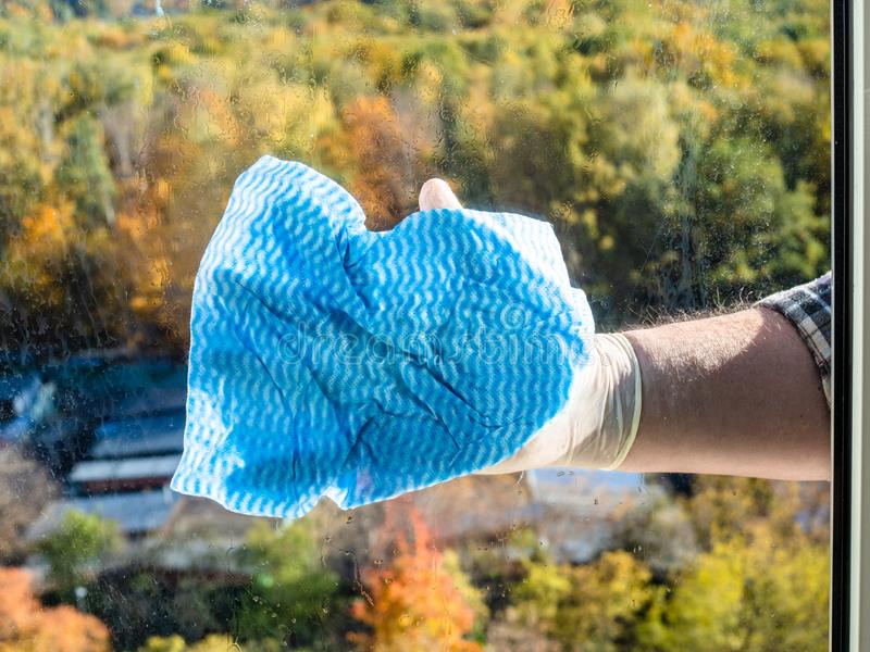 male hand washes home window glass by blue rag royalty free stock images