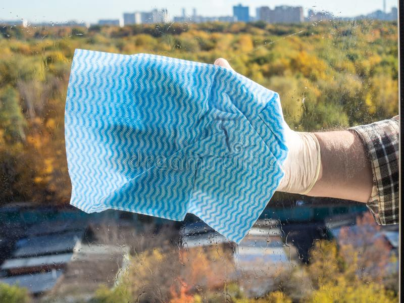 male hand washes window glass by blue rag royalty free stock images