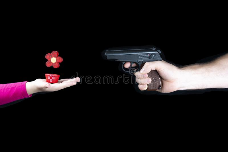Male hand with a weapon against a child s hand with a red flower, stop weapon, stop war royalty free stock photos