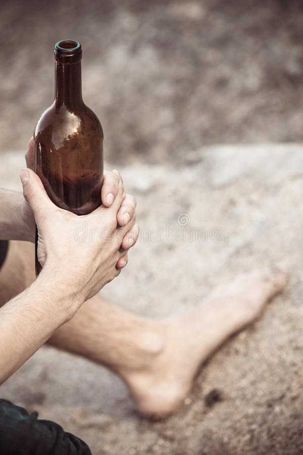 Male hand with wine bottle outdoor. Man depressed holding wine bottle sitting on sea shore outdoor. People abuse and alcoholism problems royalty free stock photo