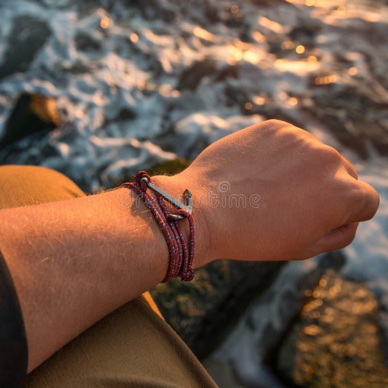 Free Male Hand With Silver Anchor Bracelet On Ocean Beach Rocks Stock Photos - 77375813