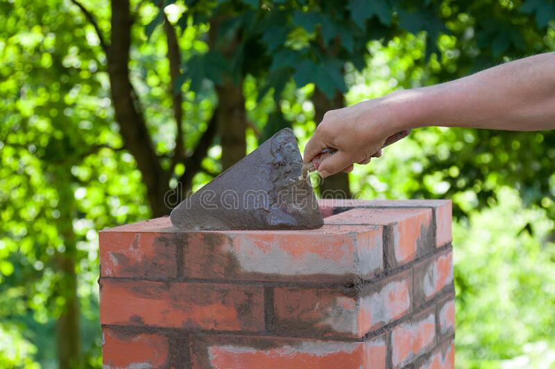 Male hand working with a trowel, repairing a chimney from red bricks on a roof royalty free stock photos
