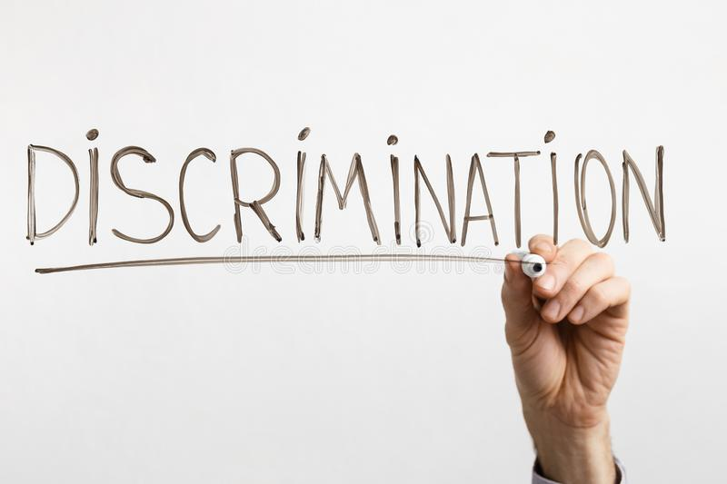 Male hand writing inscription Discrimination with marker royalty free stock photos