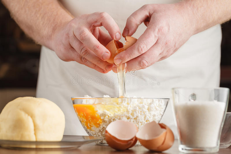 Male hands breaking eggs into a bowl; closeup stock photo