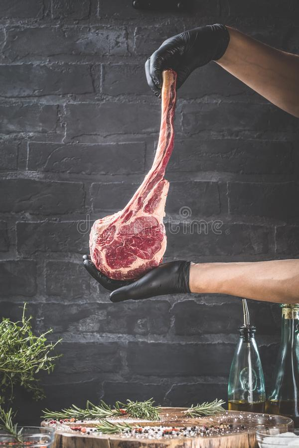 Male hands of butcher or cook holding tomahawk beef steak on dark rustic kitchen table background royalty free stock photos