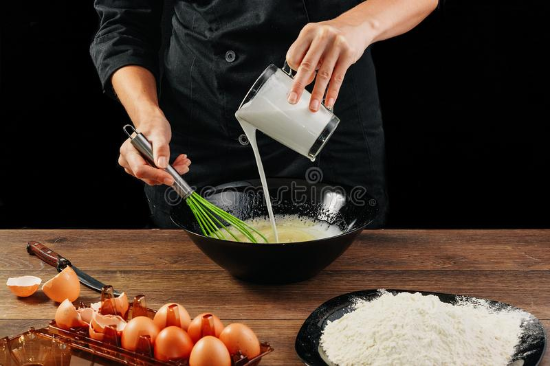 Male hands chef pours the milk into a plate on a wooden brown table in a black bowl. Chef kneads the dough. Black background. The royalty free stock photos