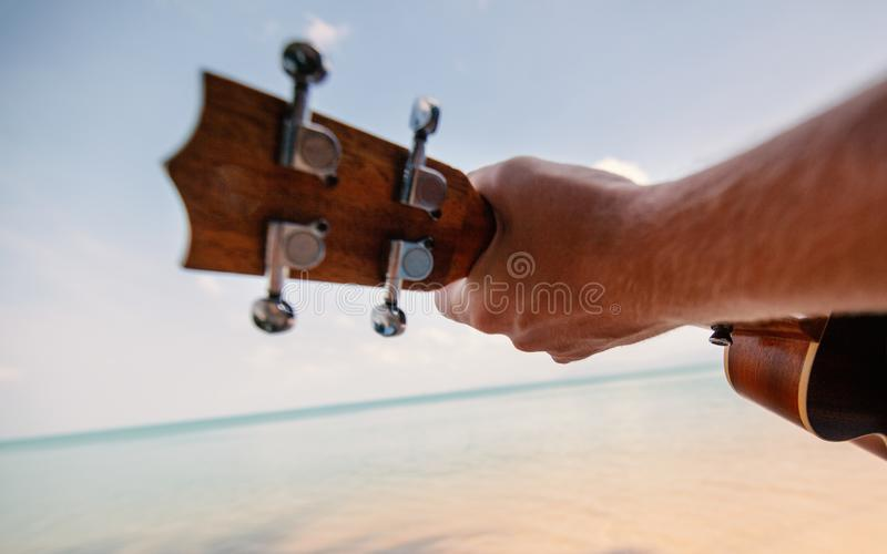 Male hands closeup, man playing ukulele on tropical beach, music, art, travel and vacation concept royalty free stock photo