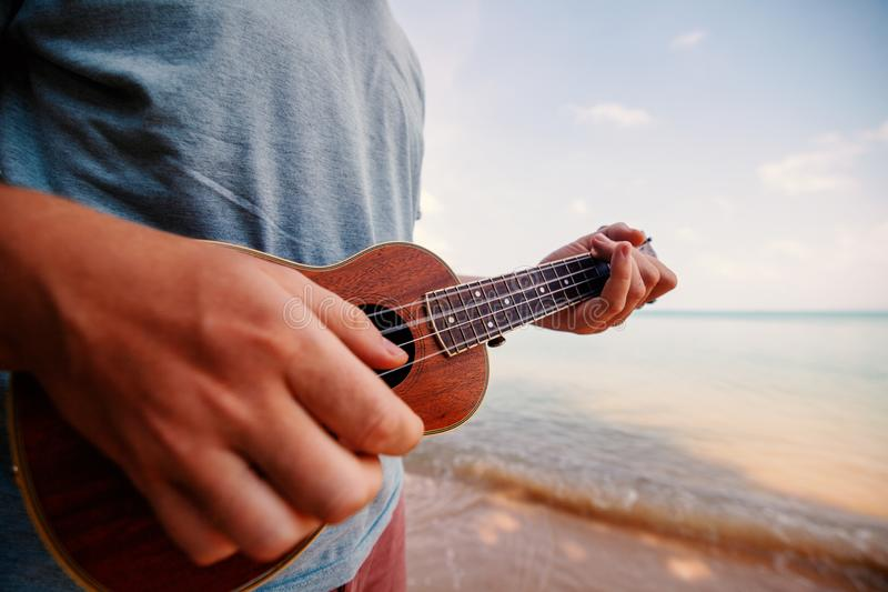 Male hands closeup, man playing ukulele on tropical beach, music, art, travel and vacation concept. Male hands closeup, man playing ukulele on tropical beach stock photo