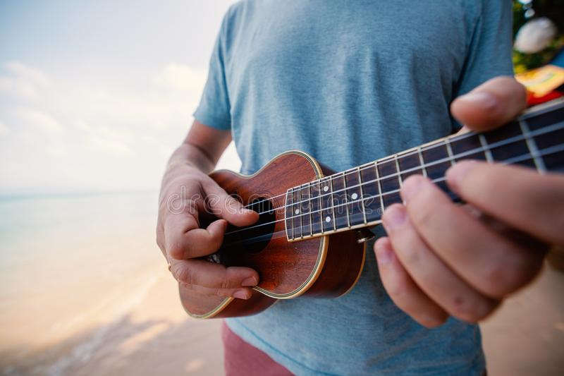 Male hands closeup, man playing ukulele on tropical beach, music, art, travel and vacation concept. Male hands closeup, man playing ukulele on tropical beach stock image