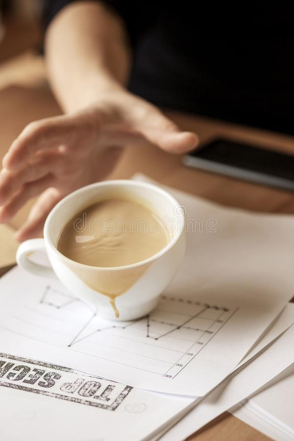 Coffee in white cup spilling on the table in the morning working day at office table. The male hands and coffee in white cup spilling in slow motion or movement stock photography
