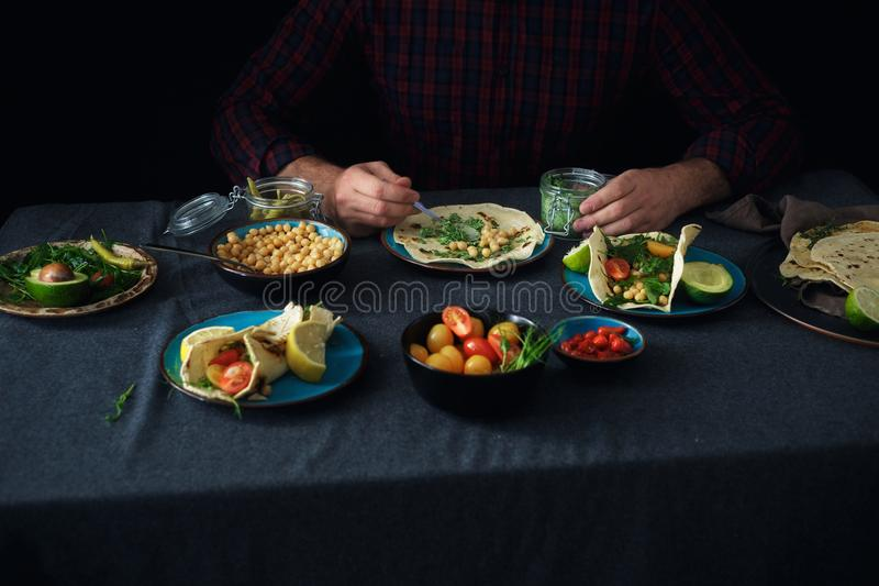 Male hands cooking vegetarian tortilla with variety dip royalty free stock image