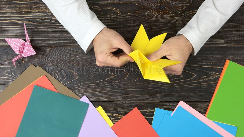 Male hands folding yellow paper sheet. Pink orizuru paper figurine on wooden table, top view. Creativity and artwork concept stock photo