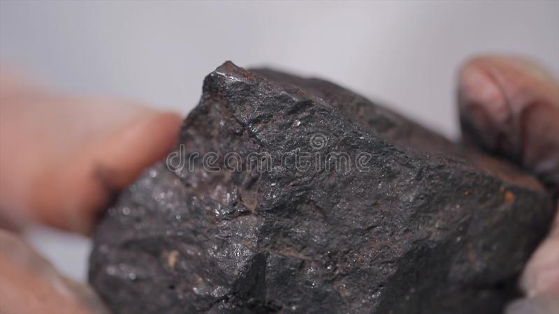 Male hands in gloves holding coal. Scientist with a sample of coal. Black coal in miner`s hand stock images