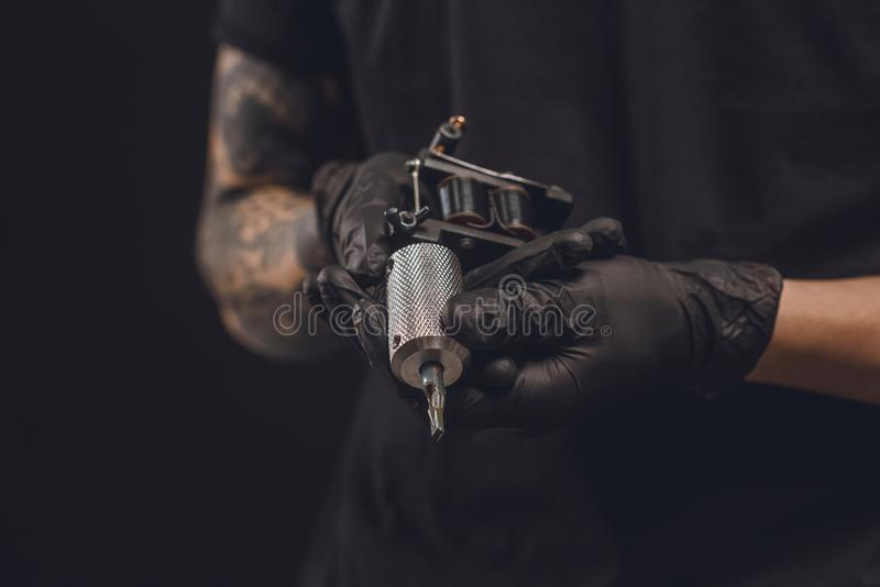 Male hands in gloves holding tattoo machine. On black stock photos