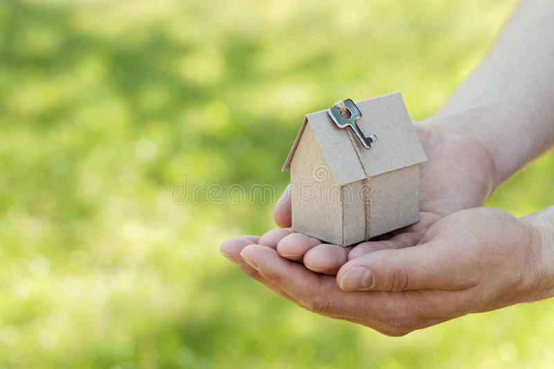 Male hands hold of cardboard house against green bokeh. Building, loan, housewarming, insurance, real estate or buying new home. stock photo