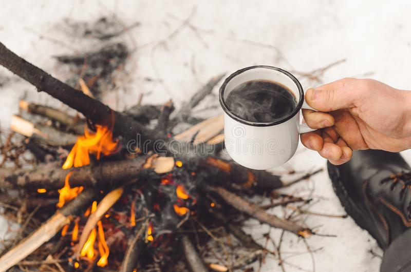 Male hands hold a mug of coffee near a burning campfire. Concept hike, walk, trip in winter. royalty free stock photography