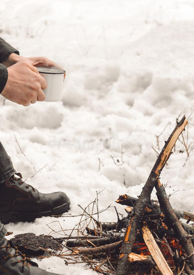 Male hands hold a mug of coffee near a burning campfire. Concept hike, walk, trip in winter. stock images