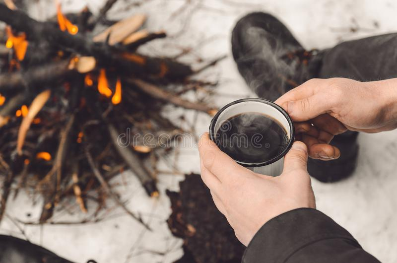 Male hands hold a mug of coffee near a burning campfire. Concept hike, walk, trip in winter royalty free stock photography