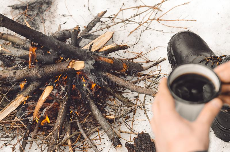 Male hands hold a mug of coffee near a burning campfire. Concept hike, walk, trip in winter. royalty free stock photo