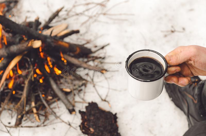 Male hands hold a mug of coffee near a burning campfire. Concept hike, walk, trip in winter stock photo