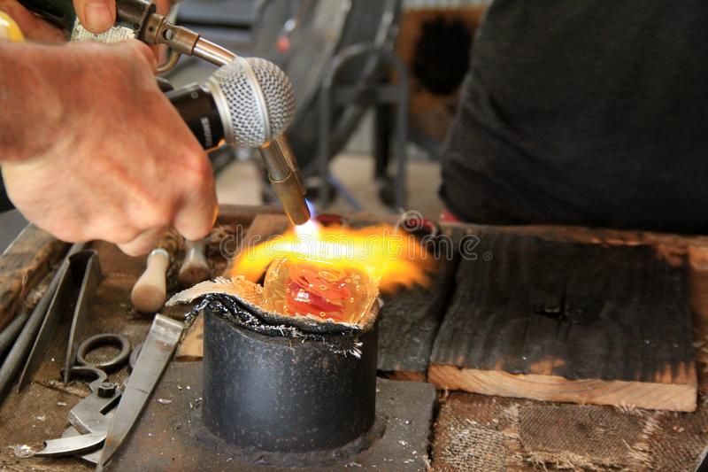 Male hands holding blow torch while fashioning item from molten glass. Male hands holding red-hot blow torch while melting glass to make items for sale in glass royalty free stock photos