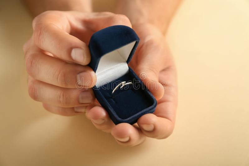 Male hands holding box with engagement ring on color background stock images