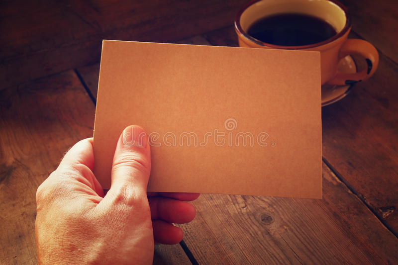 Male hands holding brown empty card over wooden table background and cup of coffee. retro style image, low key and warm tones stock photos