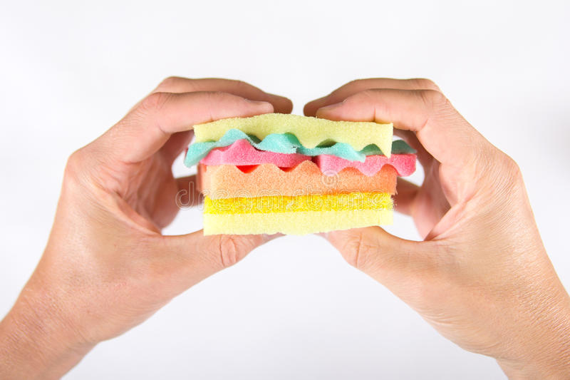 Male hands holding a burger made from sponges different colors. Concept of unhealthy food and non-natural products. Male hands holding a burger made from sponges royalty free stock images