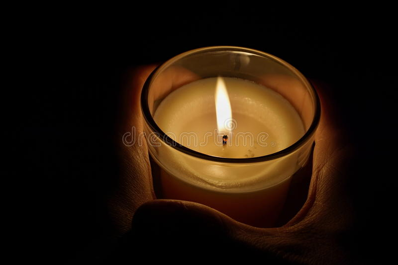 Male hands holding a candle in the transparent glass shining in the darkness as a symbol of contemplation, meditation and calmness royalty free stock photography
