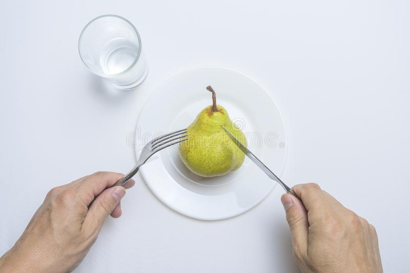 Male hands holding fork and knife on a plate with a pear on a white table stock photos