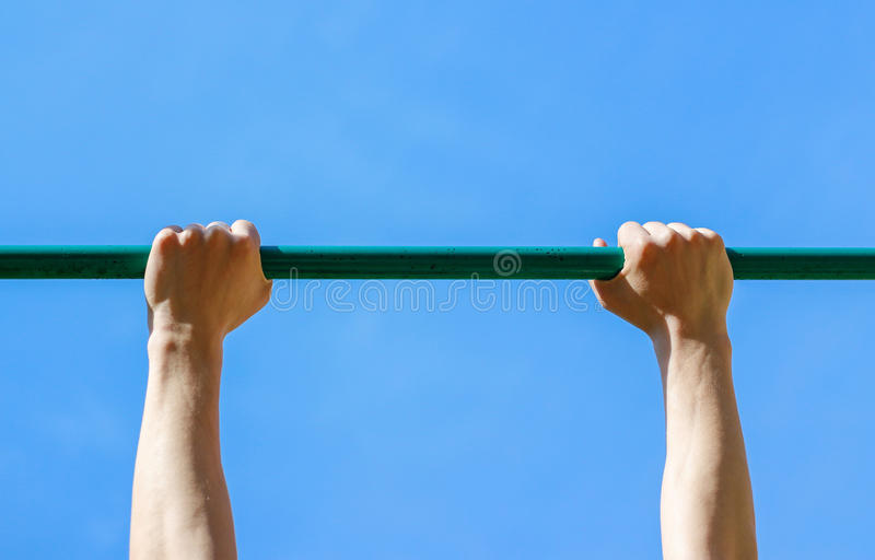 Male hands holding the horizontal bar stock photos