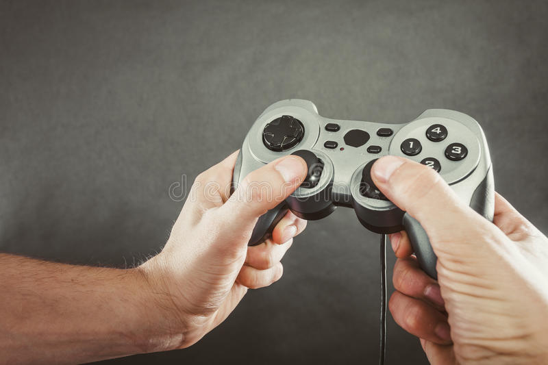 Male hands holding joystick pad. Playing games concept. Part body man with joystick play game on console playstation. Male hands holding grey pad royalty free stock photos