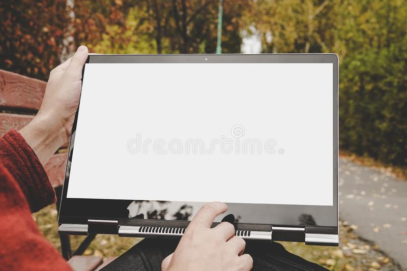 male hands holding a laptop with a touch screen and pointing at a blank white screen. Freelancer working outdoors in the Park royalty free stock photo
