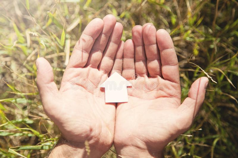 Male hands holding paper house model in nature stock image