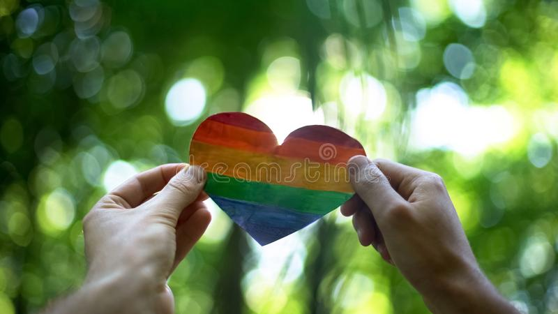 Male hands holding rainbow heart, global recognition of same-sex marriage stock images