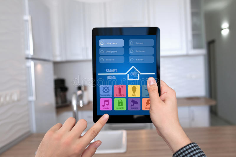 Male hands holding tablet with app smart home kitchen house. Male hands holding tablet with app smart home on background kitchen in house stock image