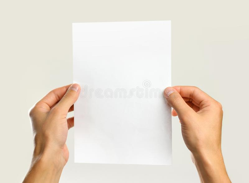 Male hands holding a white sheet of paper. Isolated on gray back royalty free stock photography