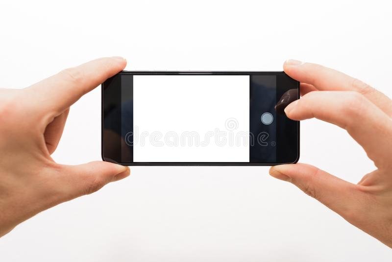 Male hands horizontally holding a smartphone ready to take a picture isolated on white royalty free stock image