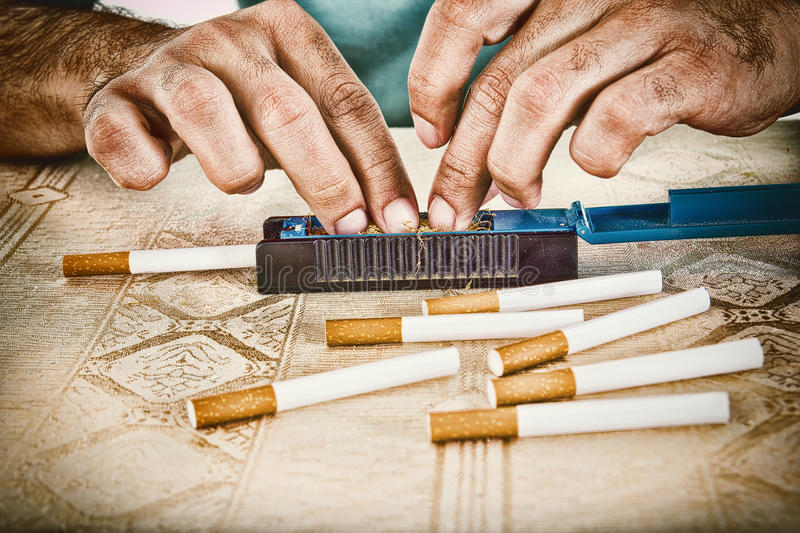 Male hands making cigars with tobacco. Male hands making cigars with rollings filled with tobacco to satisfy his habit and to smoke handmade cigarettes royalty free stock photo