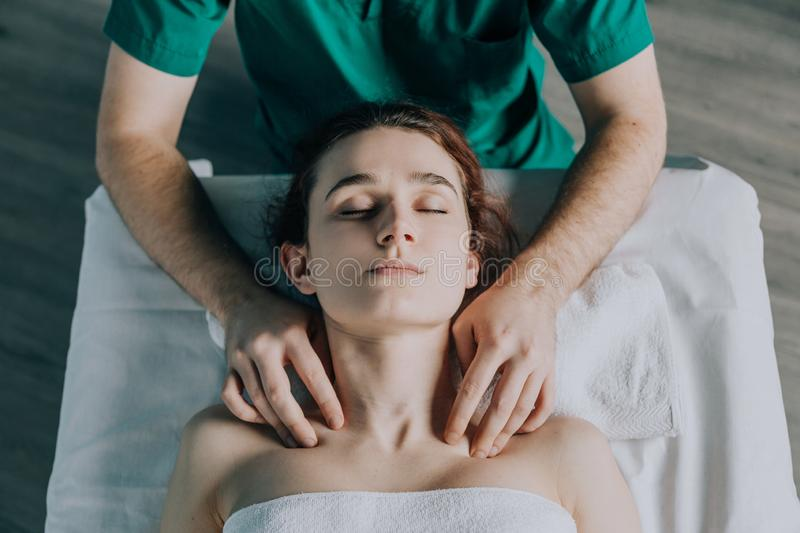 The male hands of the masseur massage the shoulder girdle and neck to a young woman. stock photos