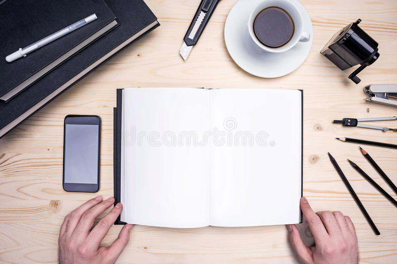 Male hands, notepad and stationery. Top view of wooden desktop with male hands, open empty notepad, smart phone, coffee and stationery. Mock up stock photo