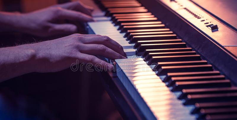 male hands on the piano keys closeup of a beautiful colorful background stock images