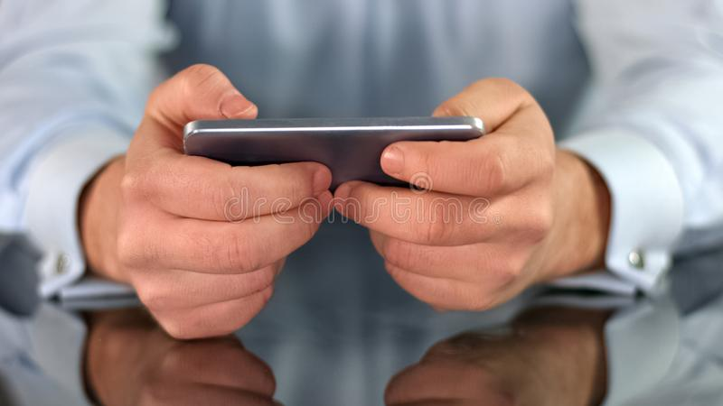 Male hands playing game on smartphone, fingers touching screen, gadget addiction. Stock photo royalty free stock photography