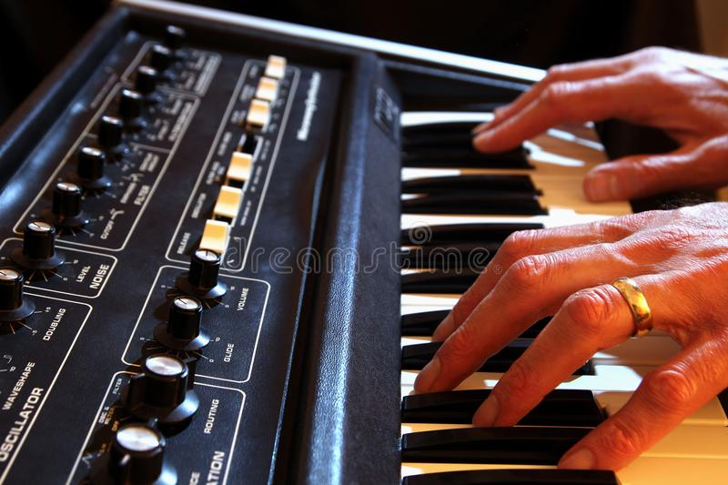 Male hands playing a vintage analogue synth in shallow focus stock photo