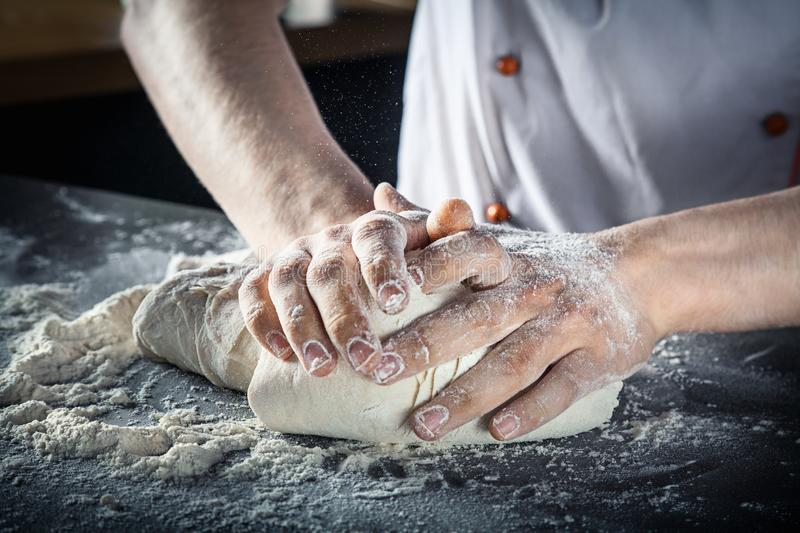 Male hands preparing pizza dough. chef in kitchen prepares the dough for gluten free pasta or bakery. baker kneads dough on the stock photos